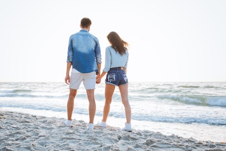 Back view of a happy young couple walking and holding hands at the beach Stock Photo