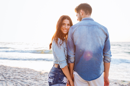 backwards: Beautiful young woman holding her boyfriend hand who standing backwards at the beach Stock Photo