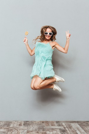 Happy charming young woman in sunglasses jumping in the air Stock Photo