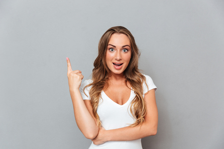 pointing finger up: Attractive young woman pointing finger up over gray background