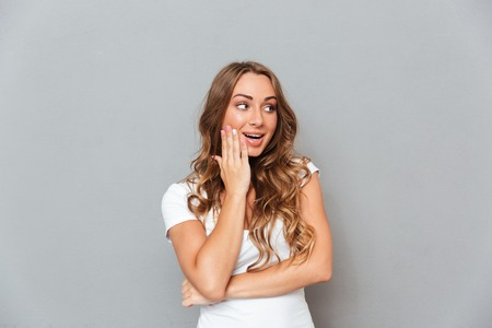disbelief: Portrait of happy surprised young woman with opened mouth over grey background