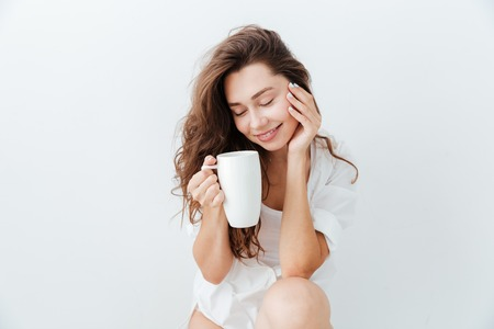 Beautiful young lovely girl with cup of tea sitting and resting isolated over white background Stock Photo