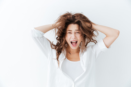 bad hair day: Young brunette woman with long hair shouting isolated on a white background