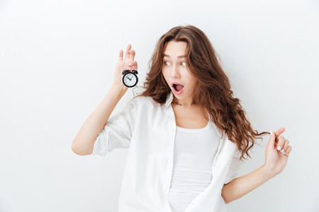 Cute amazed young girl looking at alarm clock over white background Stock Photo