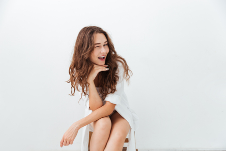 Beautiful young smiling girl winking isolated on the white background