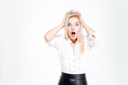 hands over ears: Young blonde businesswoman shouting and covering her ears with hands over white background