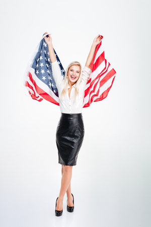 Full length of happy attractive young businesswoman holding big flag of America over white background Stock Photo