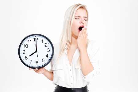 keep an eye on: Tired businesswoman yawning and holding clock isolated on a white background