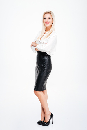 Full length of happy pretty young businesswoman standing with arms crossed over white background