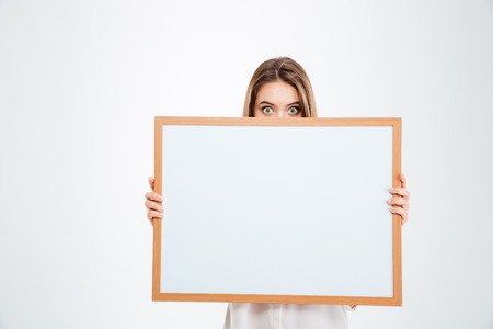 eyes wide: Young woman with eyes wide open peeping from blank board isolated on a white background Stock Photo