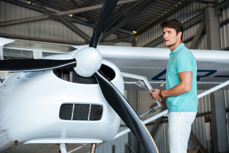 private airplane: Attractive young man pilot standing near small private airplane Stock Photo