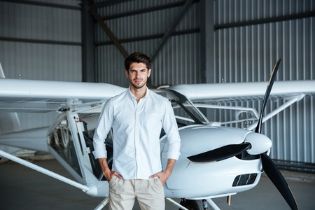 private parts: Confident attractive young man standing in front of small aircraft