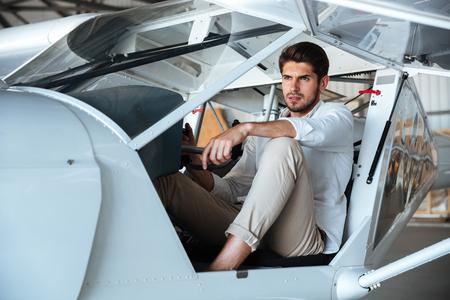 Ritratto di giovane attraente pilota in piccolo aereo