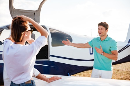 private airplane: Cheerful young pilot inviting passengers on board of private airplane