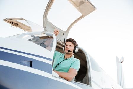 Portrait de jeune homme confiant pilote dans un petit avion