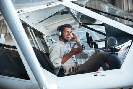 small plane: Happy young man pilot sitting in small plane and talking using headset