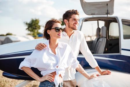 Portrait d'un jeune couple jeune debout près d'un petit avion privé