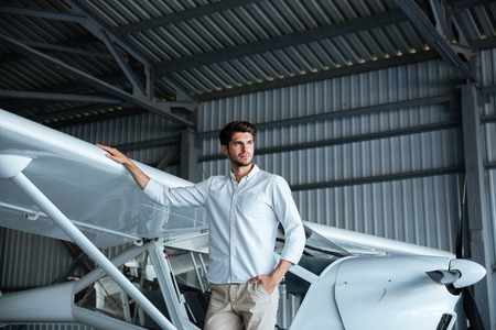 smal: Portrait of handsome young man standing near smal airplane Stock Photo