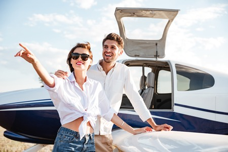 small plane: Cheerful young couple standing near small plane and pointing away