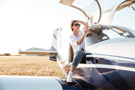 Attractive young woman in sunglasses sitting in small private plane