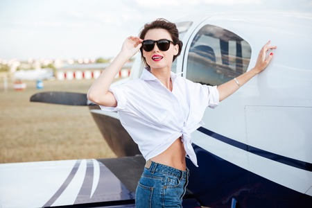 Happy charming young woman standing near private airplane