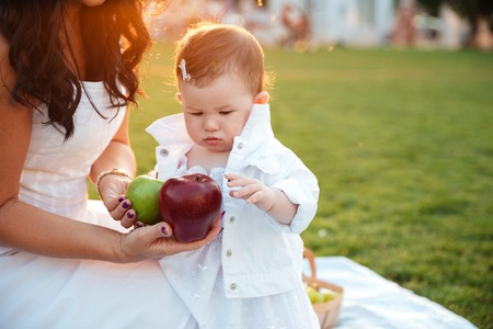 Cute little girl taking apples from her mom on picnic Stock Photo