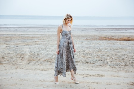 Pretty young woman in beautiful long dress walking tiptoes on the beach Stock Photo