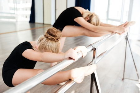 Little graceful ballerina and her teacher stretching legs with stick on wall in ballet school Stock Photo