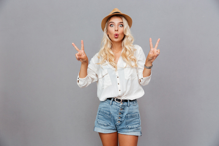 isolated sign: Funny excited young woman showing peace sign over gray background