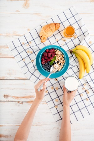 cereals holding hands: Cereal, berries, banana and croissant and plaid napkin on wooden background