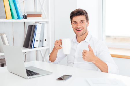 Happy smiling businessman holding tea cup and showing thumbs up while sitting at the office desk