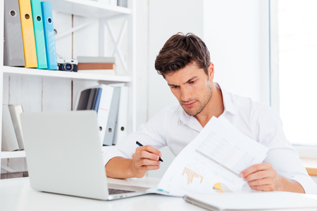 Concentrated young businessman sitting and writing at the table in office