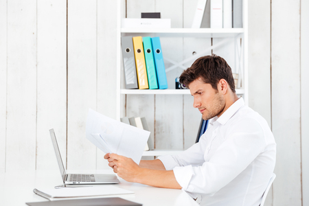 Side view of a serious young businessman working with documents at the office
