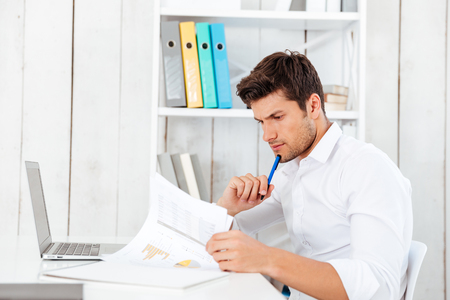 Handsome young businessman sitting and signing documents in office