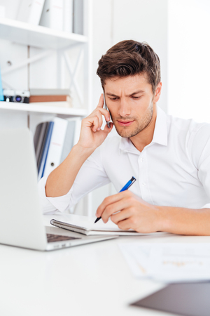 Concentrated young businessman talking on the mobile phone and making notes at workplace 스톡 콘텐츠