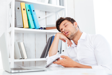 Exhausted fatigued young businessman sleeping while sitting at the office desk