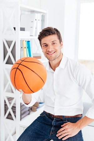 staring at the camera man: Handsome businessman sitting at the table and holding ball in office