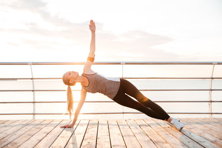 planking: Sporty fitness woman doing planking yoga exercises outdoors at the beach pier