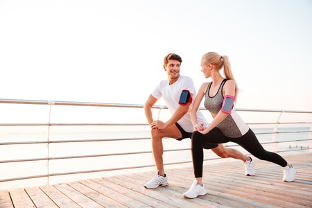Athletic young couple doing stretching legs exercises together on the pier