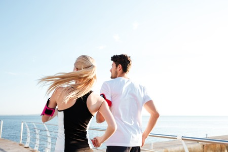 Back view of a couple exercising for marathon and workout fitness at the beach pier