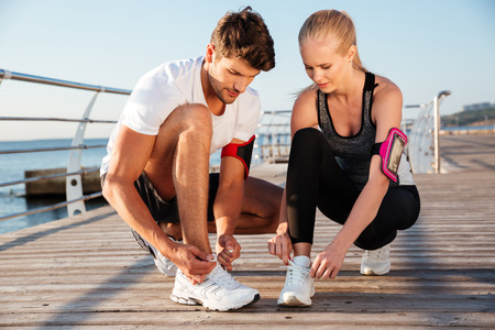 sport shoe: Top view of young man and woman tying shoelaces while standing outdoors Stock Photo