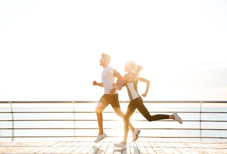 Jong sportief paar dat over houten pijler bij zonsondergang loopt Stockfoto - 65119113