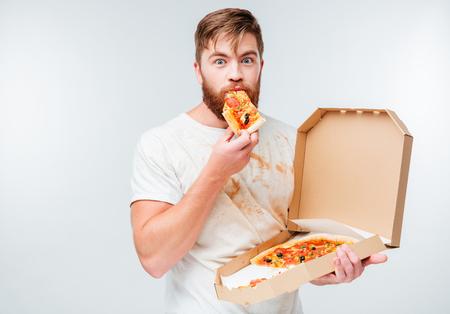 Gelukkige hongerige mens die pizza van een doos eet die op witte achtergrond wordt geïsoleerd