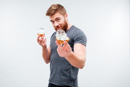 Attraktiver bärtiger Mann , der Creme Kuchen lokalisiert auf weißem Hintergrund zeigt Standard-Bild