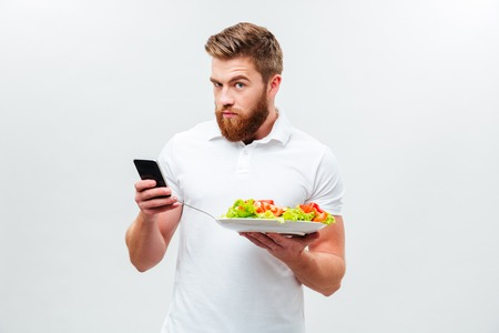 plato del buen comer: Young bearded man holding plate with vegetable and using mobile phone isolated on the white background Foto de archivo