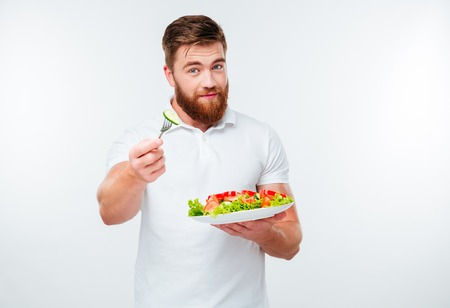 healthy men: Young bearded man eating salad isolated on white background