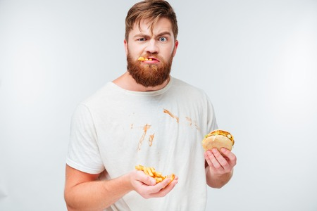 aliments droles: Funny hungry bearded man eating junk food isolated on white background