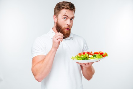 Happy excited bearded man holding plate with fresh sala a, Stock Photo