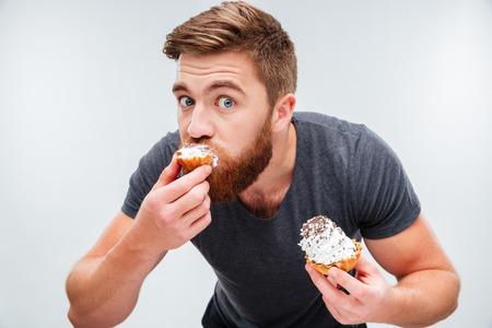 흰색 배경에 고립 된 크림 케이크를 물고 배고픈 수염 난된 남자의 초상화를 닫습니다