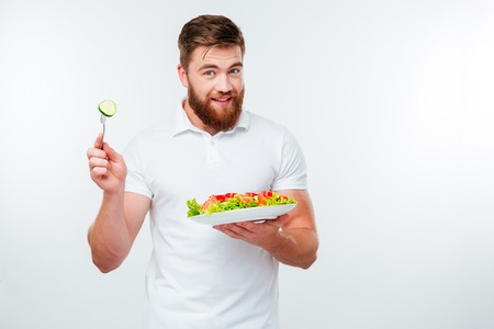 healthy men: Young smiling man holding fork to eat fresh vegetable salad meal isolated on white background